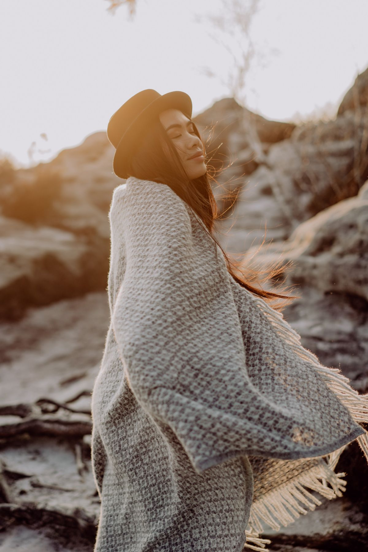 Porträtfotograf mit Model mit Hut und Decke im Sonnenuntergang