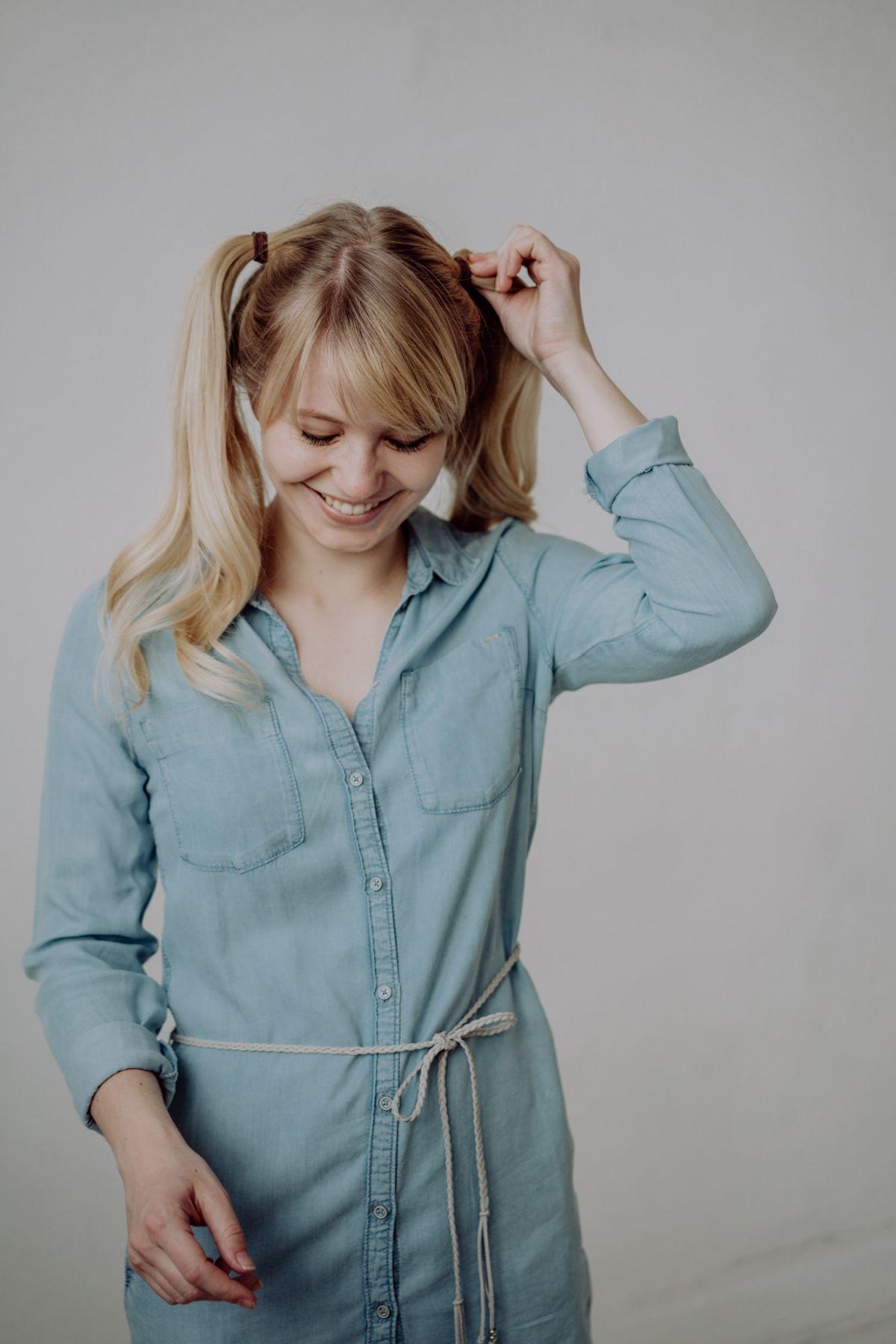 Blonde junge Frau mit langen Zöpfen lachend vor weißem Hintergrund, Leipzig ISO-Studios